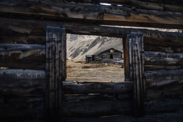 An abandoned mining cabin viewed from inside another cabin in Colorado.