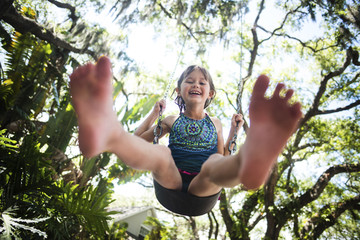 Low angle portrait of cheerful girl swinging in forest