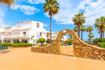 Gate to park and white houses with tropical plants in small coastal village near Marbella, Costa del Sol, Spain
