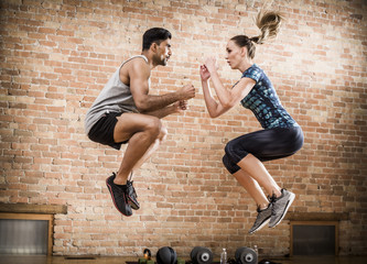 Side view of confident athletes jumping against brick wall in gym