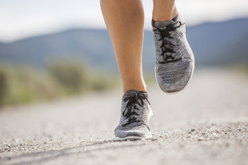 Low section of woman wearing shoes jogging on road