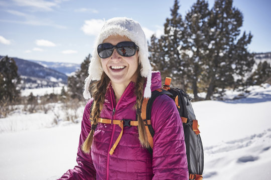 Portrait of female hiker wearing sunglasses and hunter cap standing on mountain