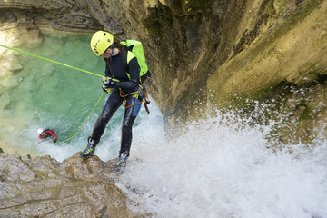 High angle view of hikers rappelling amidst waterfall on canyons