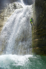 Low angle view of female hiker rappelling on canyon amidst waterfall