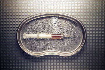 Overhead view of syringe in wet tray on metallic table