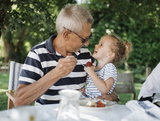 Grandfather feeding strawberry to granddaughter while sitting at table in yard