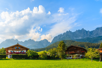 Wall Mural - Traditional houses on green meadow in Going am Wilden Kaiser mountain village, Kitzbuhel Alps, Austria