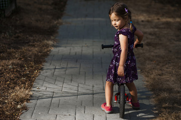 Side view of girl with bicycle standing on footpath at park
