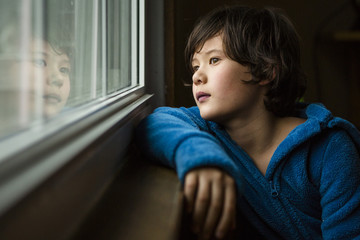 Thoughtful boy looking through window while sitting at home