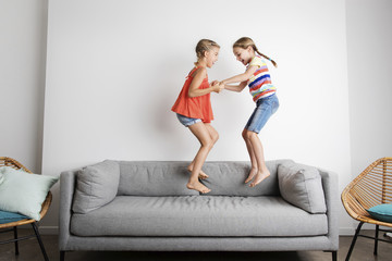 Happy sisters holding hands while jumping on sofa against wall at home