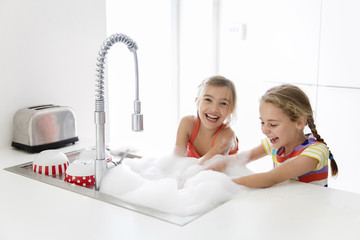 Happy sisters washing dishes in kitchen sink at home