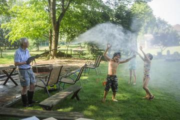 Grandfather spraying water on playful grandchildren at yard