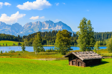 Wall Mural - Wooden hut on green meadow against Alps mountains near Schwarzsee lake on sunny beautiful summer day near Kitzbuhel, Tyrol, Austria