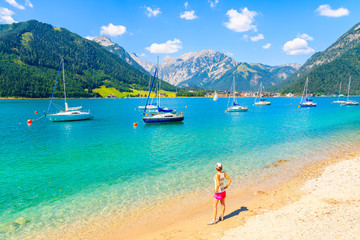 Young woman tourist standing on beautiful Achensee lake beach on sunny summer day, Tirol, Austria