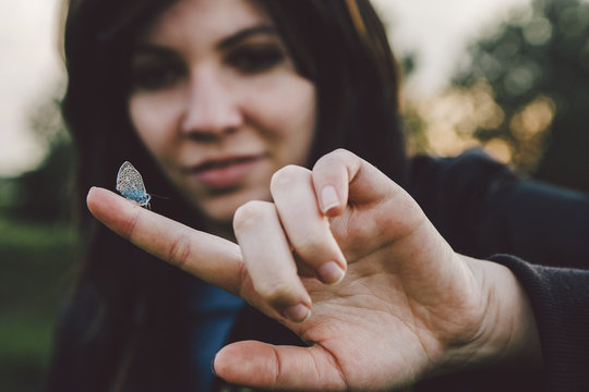 Close up of butterfly sitting on woman's finger in park