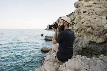 Bearded man photographing with camera sitting on rock near sea