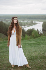 Hippie girl in white dress and velvet jacket in nature. Freedom and lifestyle. Retro clothing and accessories. The landscape of fields and river.