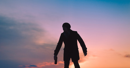 A drunk young man is walking staggering down the street. Silhouette of a Drunkard. A guy with a bottle of alcohol in his hand. Copy space.