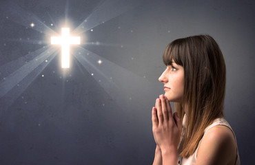 Young woman praying on a grey background with a shiny cross above her