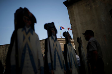 The Puerto Rican flag is seen at half mast during a commemorative event organized by the local government a year after Hurricane Maria devastated Puerto Rico, in San Juan, Puerto Rico