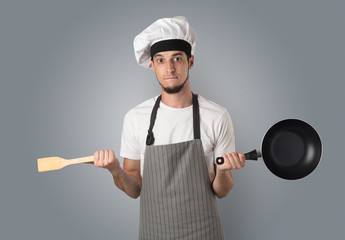 Young bearded cook portrait with kitchen tools and empty wallpaper