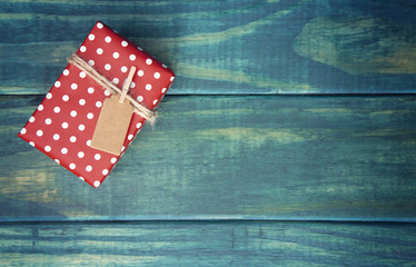 Single Wrapped Christmas Present with Gift Tag on a Wooden Table