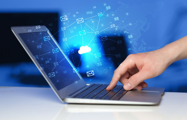 Hand using laptop with cloud computing and online storage concept