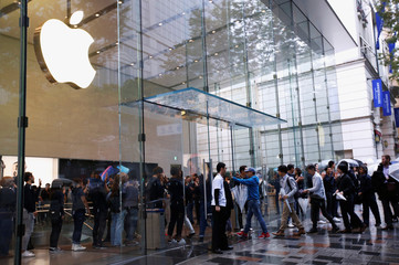 Apple Store staff greets customers who have been waiting in line to purchase Apple's new iPhone XS and XS Max at the Apple Store in Tokyo