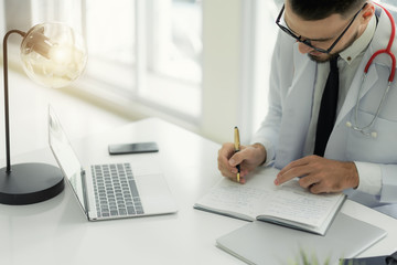 Doctor working with laptop computer and writing on paperwork with physician's stethoscope on desk in the hospital.
