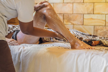 Young woman gets scrub massage in spa salon