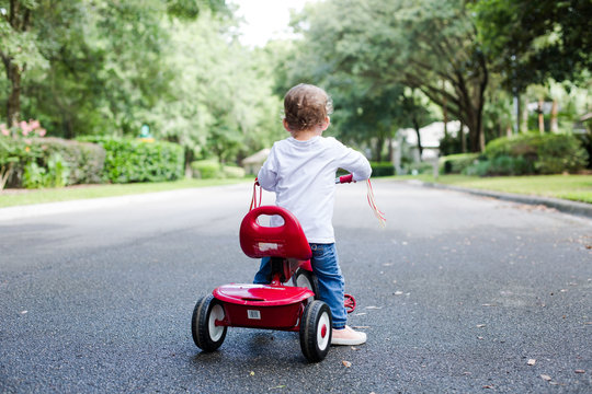 Young Child Toddler on Red Tricycle on a Neighborhood Street
