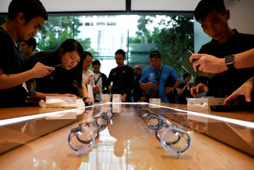 Customers look at the new Apple Watch Series 4 displayed at the Apple Store in Singapore