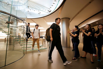Staffs welcome the customers after Apple's new iPhone XS and XS Max went on sale at the Apple Store in Beijing