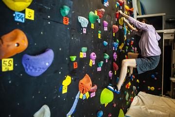 ボルダリングジムで真剣に壁を登る女性
