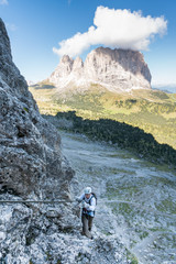 young attractive male mountain climber in the Dolomites of italy with a great panorama view of the Langkofel and Passo Sella