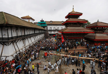 "Devotees erect a ""lingo"", a long wooden pole, at Hanumandhoka Durbar Square to mark the beginning of the Indra Jatra Festival in Kathmandu"