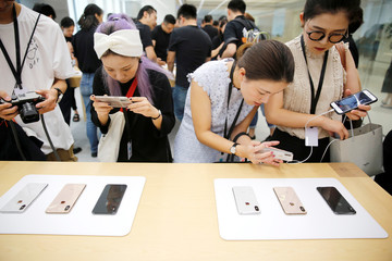 People experience new Apple's iPhone XS and iPhone XS Max during a media tour at an Apple office in Shanghai