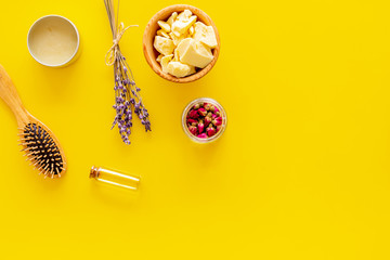 Hair treatment with natural products. Jojoba, argan, coconut oil near bunch of lavender and hairbrush on yellow background top view copy space