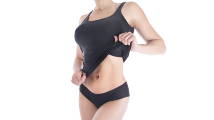 Female sporty body in black underwear, isolated on white, woman holds her top and shows her waist, good shape