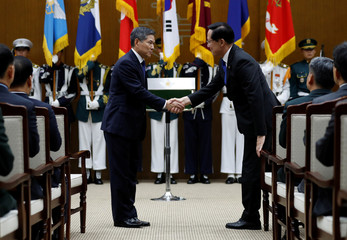 Ingoing Defense Minister Jeong Kyeong-doo shakes hands with outgoing Minister Song Young-moo during his inaugural ceremony at Defense Ministry in Seoul