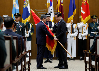 Outgoing Minister Song Young-moo hands the flag of the Defense Ministry over to Ingoing Defense Minister Jeong Kyeong-doo during his inaugural ceremony at the Defense Ministry in Seoul