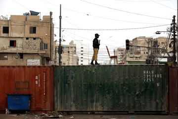 A policeman stands guard on a shipping container used to block roads, as added security is put in place, during a religious procession to mark Ashura in Karachi