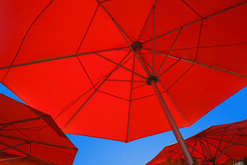 Close up of three red cafe umbrellas filling the frame and blue sky between them. Patio umbrellas as seen from bottom