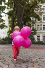 Little kid with pink ballons in hand. Kleinkind mit Luftballon in Hand.