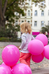 Blondes Kind mit Luftballon in Hand. Blond child with pink ballons in hand.