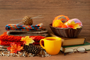 Knitting and autumn. Yarn, a cup of tea, knitting needles, glasses, books for knitting in a cozy atmosphere. Maple leaves and spruce cones are reminiscent of autumn. Knitting warm clothes.