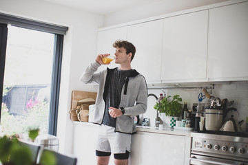 Young adult male drinking orange juice before after a run