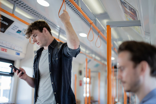 Commuter using smartphone on train