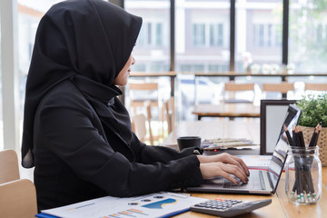 Young muslim business woman wearing black hijab,working in coworking.