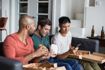 Male friends eating different takeout meals together